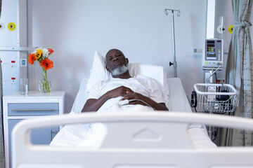 Portrait of african american male patient lying on hospital bed looking to camera