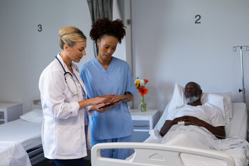 Two diverse female doctors standing next to african american male in patient room looking at tablet