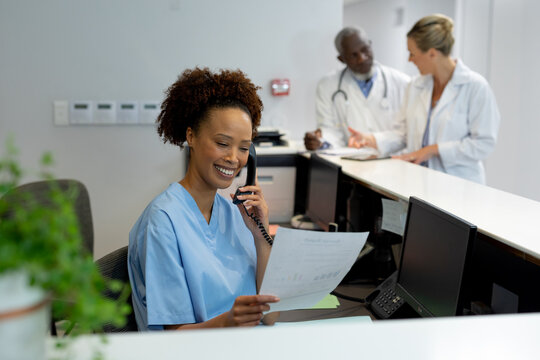 Mixed race female doctor at desk in hospital reception talking on phone and holding document