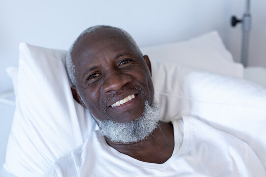 Portrait of african american male patient lying on hospital bed smiling to camera