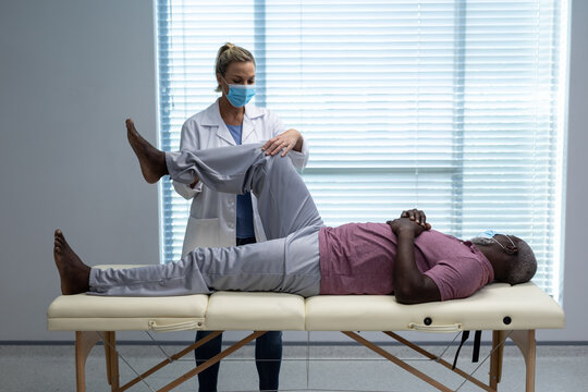 Caucasian female physiotherapist wearing face mask bending knee of african american male patient