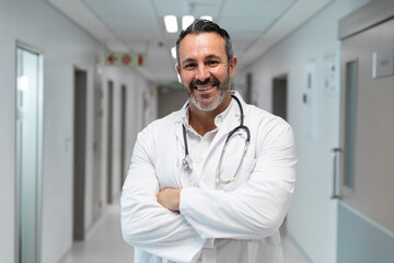 Portrait of mixed race male doctor smiling and standing in hospital corridor