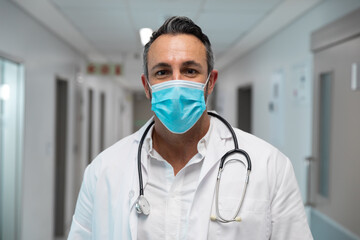 Portrait of mixed race male doctor wearing face mask standing in hospital corridor