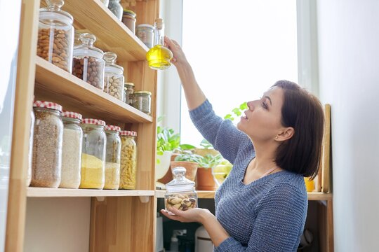 Organization of pantry, woman in kitchen near wooden rack with cans and containers of food