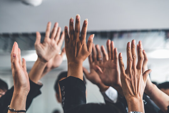 Many happy business people raise hands together with joy and success. Company employee celebrate after finishing successful work project. Corporate partnership and achievement concept.