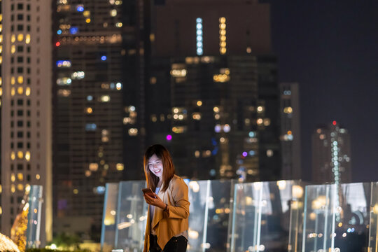 Asian businesswoman using smart mobile phone with smile action in the financial district area at bangkok river side, Thailand, technology with career concept