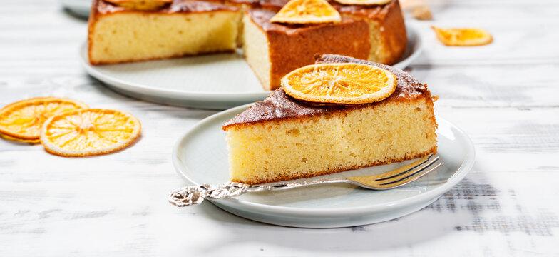 Slice of Semolina cake decorated with dried orange slices.