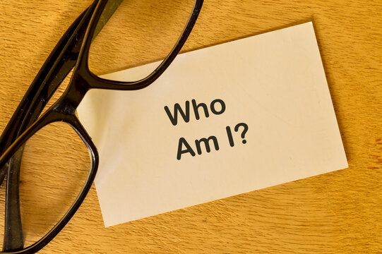 Phrase WHO AM I? written on white paper with eyeglasses.