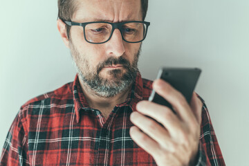 Headshot portrait of mid-adult male reading text message notification on mobile smart phone