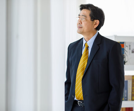 Portrait shot of Asian senior old successful company entrepreneur in formal suit with brown necktie and golden eyeglasses standing  against white background