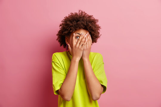 Scared dark skinned woman with natural curly hair covers face peeks through fingers tries to notice something wears casual t shirt isolated over pink bacground focused somewhere. Studio shot