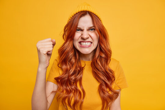 Outraged distressed redhead young European woman clenches teeth from anger cannot control her emotions being dismayed raises fist and says I will show you hates rules looks furious loses temper