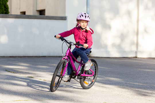One little young school age biker girl riding a bike alone in a protective helmet. Child on a bike, children and sports, physical activity outdoors, cycling, healthy lifestyle, recreation and leisure