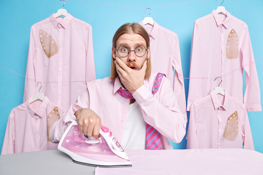 Photo of scared shocked redhead Caucasian man covers mouth stares frightened at camera forgot about one more task from wife about house poses near ironing board strokes clothes blue background