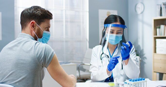 Close up of young Asian pretty female medic physician in medical mask and face shield filling syringe with covid-19 vaccine doing injection in hospital to handsome Caucasian male patient. Vaccination