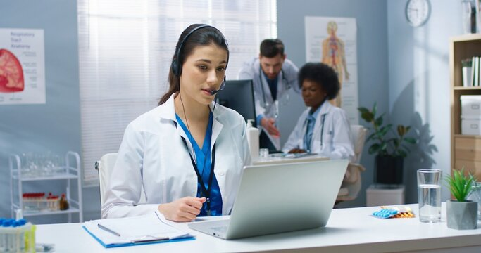 Caucasian young pretty female doctor having online video call consultation on laptop speaking in headset with patient sitting at table in hospital cabinet. Healthcare, Portrait, medical center concept