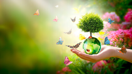 Fototapeta Earth Day or World Environment Day concept. Save our Planet, protect Green Nature and planting trees theme. Growing thuja on globe in hand, ladybugs and flock of many flying colorful butterflies.