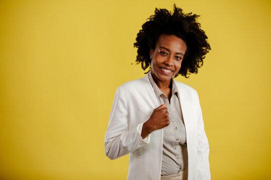 Black businesswoman standing on yellow background. Serious entrepreneur team leader mentor posing.