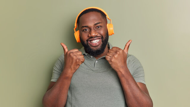 Positive dark skinned bearded man likes playlist keeps thumbs up makes approval gesture listens music via headphones smiles toothily dressed in casual t shirt isolated over dark green background