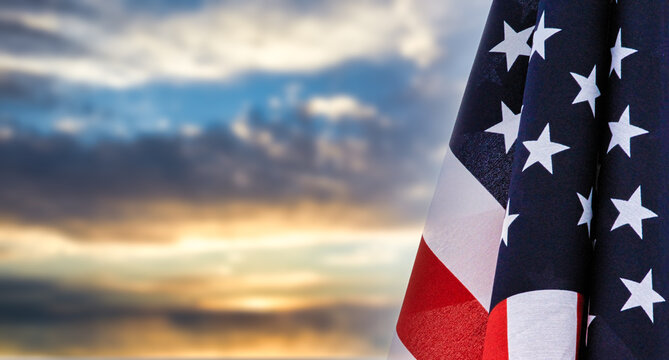 Patriotic United States of America flag at rest before a beautiful sky with room for text and cropping. Social media or web banner or header.
