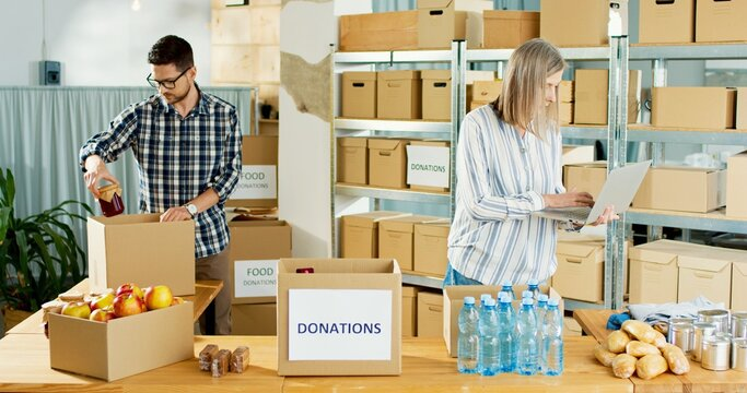 Young Caucasian male volunteer putting food in a donation box as charity worker and member of the community work to the poor. Senior woman typing on laptop standing in warehouse working in charity