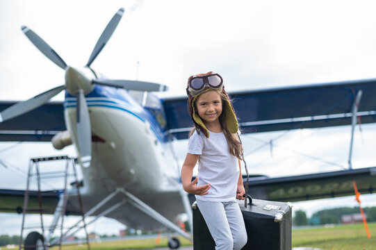 A cute little girl playing on the field by private jet dreaming of becoming a pilot