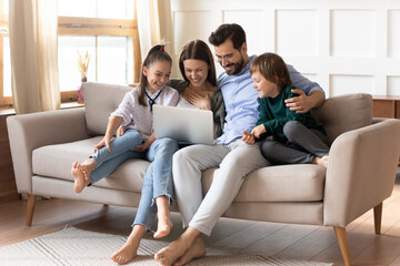 Fototapeta Happy young family with two small kids relax on sofa in living room at home have fun using laptop together. Smiling Caucasian parents with little children talk speak on webcam video call on computer.