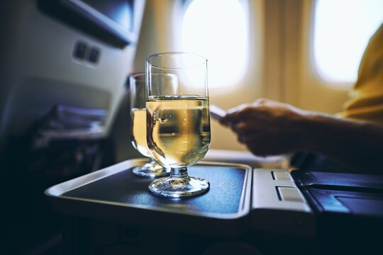 Dring during flight. Two drinking glasses of sparkling wine against airplane window.