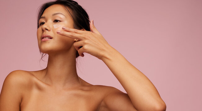 Asian woman applying anti-aging cream on her face