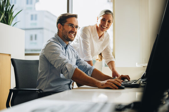 Colleagues smiling and discussing project on computer