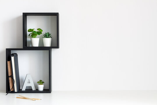 A desk against a white wall. Home office. Back to school. Copy space. Geometric composition. Square shelves.