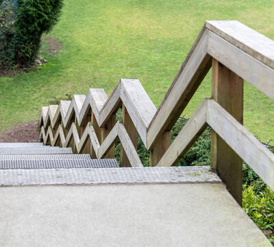 Zig-zag railings of wooden stairway on green grass background