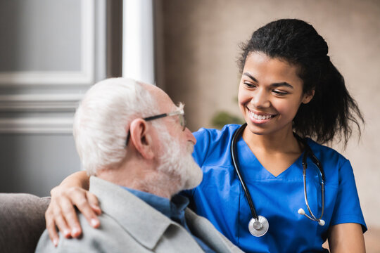 Caregiver supporting happy disabled older man sitting close up, touching shoulders, expressing care and love, smiling nurse wearing blue uniform and mature patient having fun