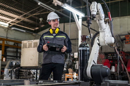 Robotics control engineers solve problems and setting programming of control panel for industrial robot arm controller in production plant factory