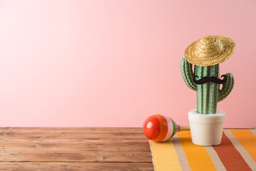 Cinco de Mayo holiday background with Mexican cactus, party sombrero hat and maracas on wooden table