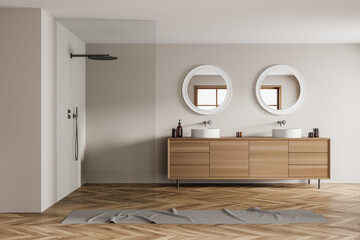 Light bathroom interior with two sinks with shower, wooden floor