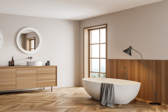 Light bathroom interior with sink and bathtub with lamp on wooden floor
