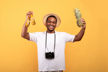 Fototapeta Portrait of handsome black guy in summer clothes with camera holding beer bottles and pineapple, looking at camera