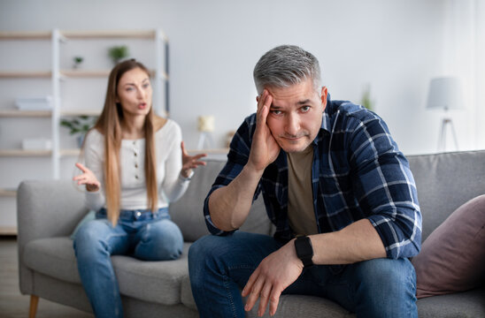 Midlife crisis and family conflicts. Mature man holding his head in stress, having fight with his angry wife at home