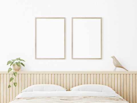 Vertical poster mockup with two wooden frames in Japandi style bedroom interior with beige slat headboard, trailing plant and bird on empty white wall background. 3D rendering, illustration