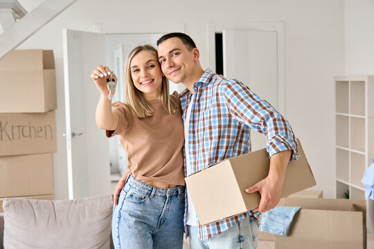 Happy young couple home owners holding keys in new home. Smiling independent millennial man and woman first time homeowners carrying boxes on moving day. Mortgage loan, new house ownership concept.