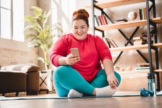 Relaxing fat plus size caucasian woman resting after hard fitness training at home using smart phone. Chubby obese woman wants to lose weight and burn calories