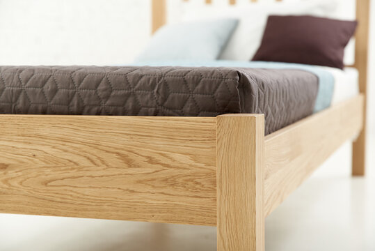 Headboard of a light ash wood bed with pillows