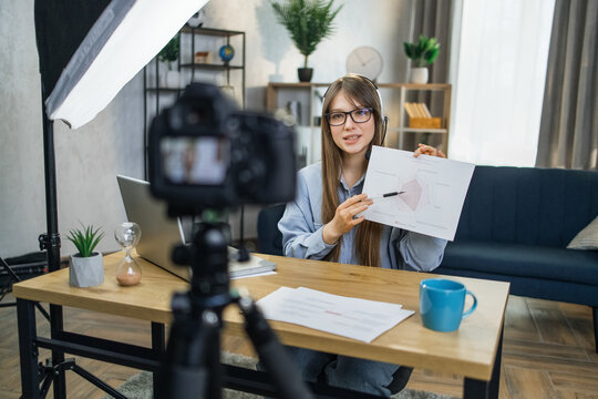 Attractive business woman in eyeglasses recording masterclass about success and finance. Pretty lady in headset using modern laptop, camera and soft box for work.