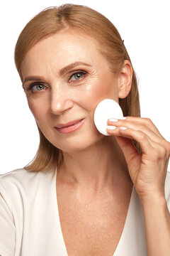Portrait of a beautiful elderly woman in a white shirt removing makeup with a cleanser and a cotton pad.