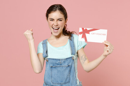 Young overjoyed caucasian woman 20s in trendy denim clothes blue t-shirt hold gift voucher flyer mock up do winner gesture isolated on pastel pink background studio portrait. People lifestyle concept