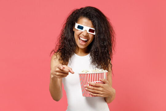 Young fun african woman in 3d glasses watch movie film, hold bucket of popcorn point index finger camera on you isolated on pink background studio portrait People emotions in cinema lifestyle concept