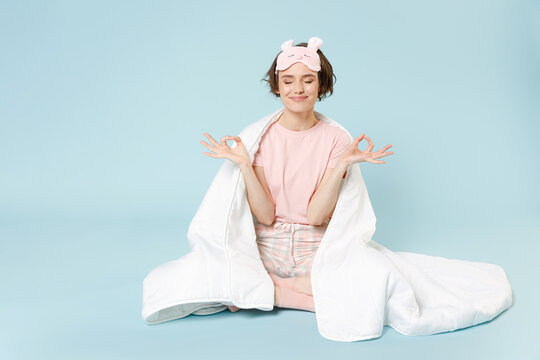 Young woman in pajamas jam sleep eye mask rest relax at home sitting wrap covered under blanket duvet do yoga om gesture calm down isolated on pastel blue background Good mood night bedtime concept.