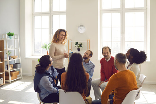 Getting psychological help in a friendly atmosphere. Professional female psychologist listens and gives advice to people at a support group meeting. People sit in a circle and share their stories.