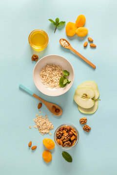 Ingredients for making breakfast with granola and fruits on blue background top view, flat lay. Cooking quick healthy breakfast concept